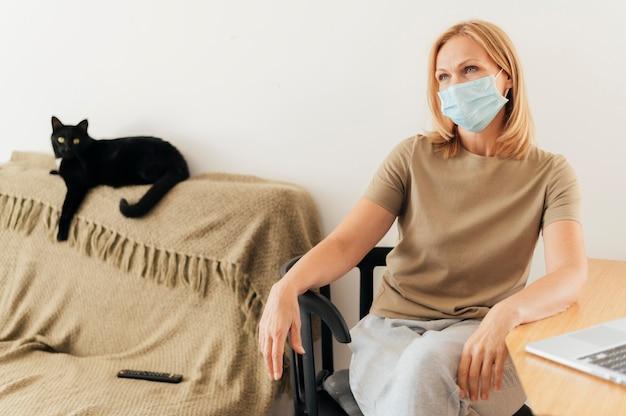 Vrouw met medisch masker thuis met kat tijdens quarantaine