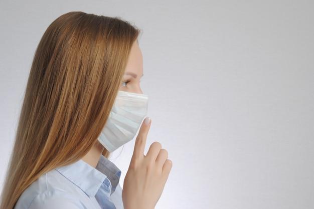 Vrouw met medisch masker toont stilte en wees stil gebaar