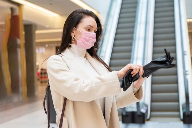 Vrouw met medisch masker trekt zwarte leren handschoenen aan in winkelcentrum of luchthaven