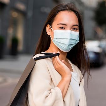Vrouw met medisch masker uit voor een koopwoede met boodschappentas