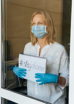 Vrouw met medisch masker verblijf thuis notebook bij het raam