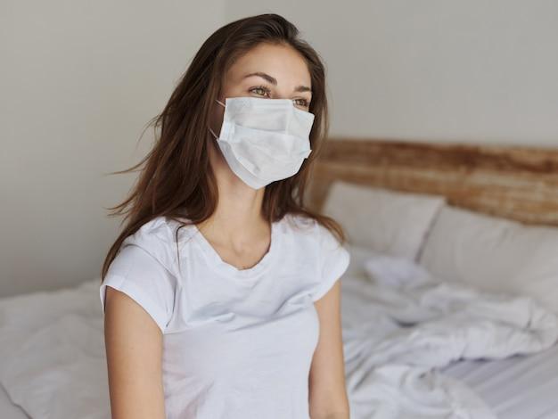Vrouw met medisch masker zittend op bed en kijkend naar de zijkant bijgesneden weergave