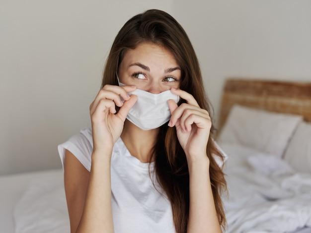 Vrouw met medisch masker zittend op bed in hotel