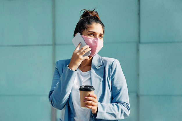 Vrouw met medische masker en koffie praten over smartphone op de luchthaven tijdens pandemie