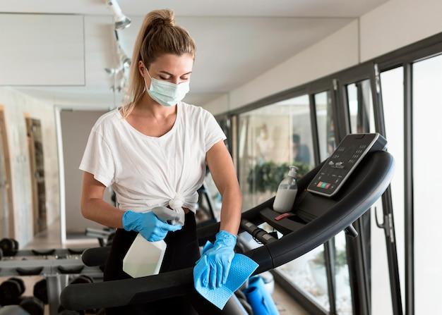 Vrouw met medische masker en reinigingsoplossing fitnessapparatuur desinfecteren