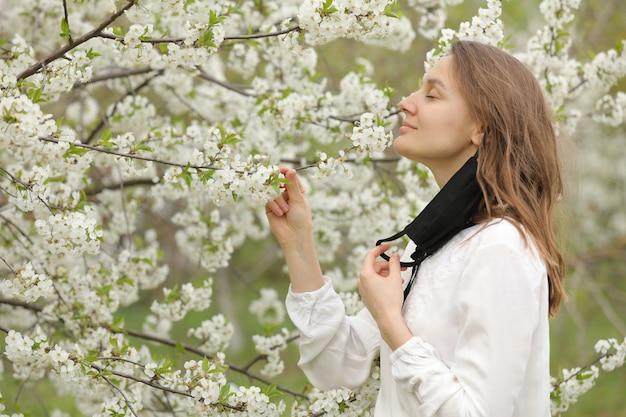 Vrouw met medische masker ruikende bomen