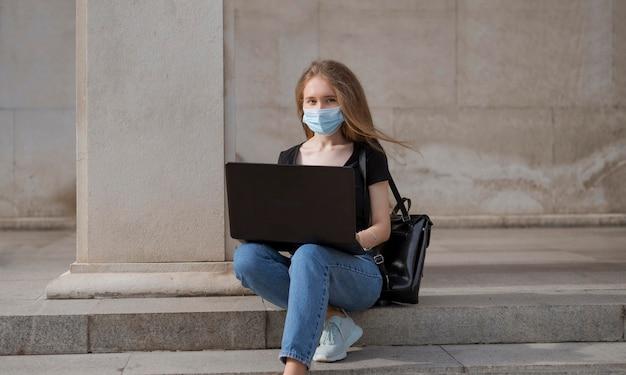 Vrouw met medische masker zittend op trappen buiten