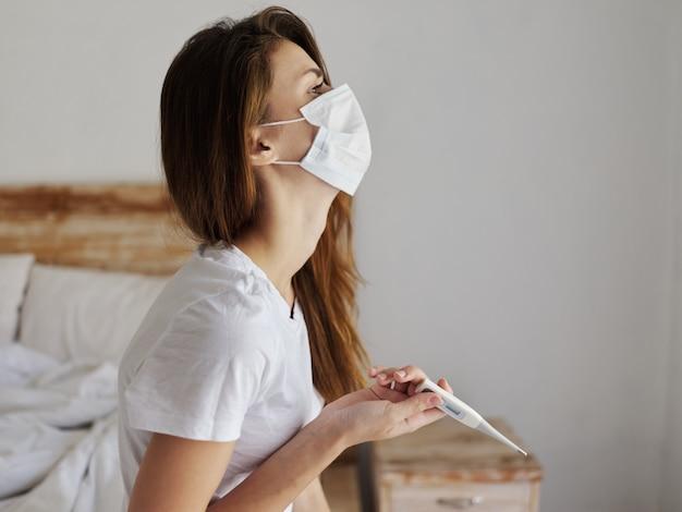Vrouw met medische maskerthermometerhanden die temperatuurgezondheidsproblemen controleren