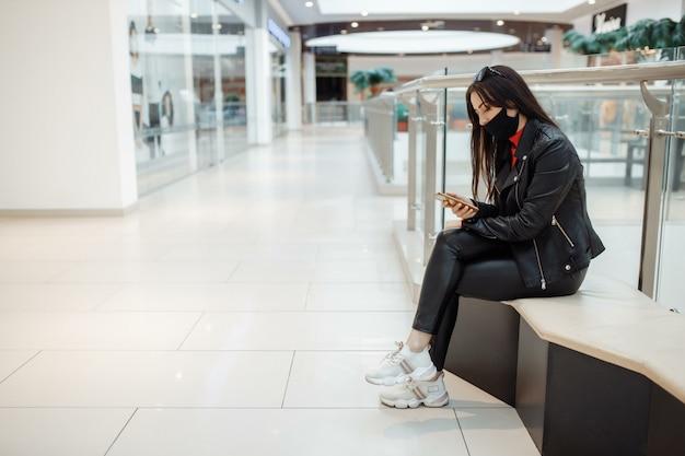 Vrouw met medische zwarte masker en mobiele telefoon in een winkelcentrum. coronapandemie. een vrouw met een masker staat in een winkelcentrum. een vrouw met een beschermend masker winkelt in het winkelcentrum