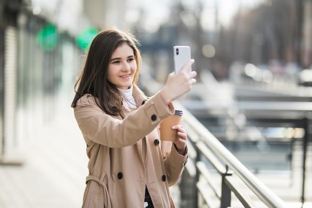 Vrouw met meeneemkoffie die een selfie in openlucht met smartphone nemen