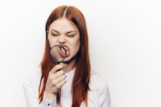 Vrouw met meer magnifier vergrootglas, witte muur.
