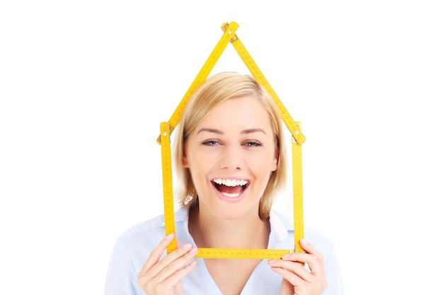 Vrouw met meetlint in huisvorm