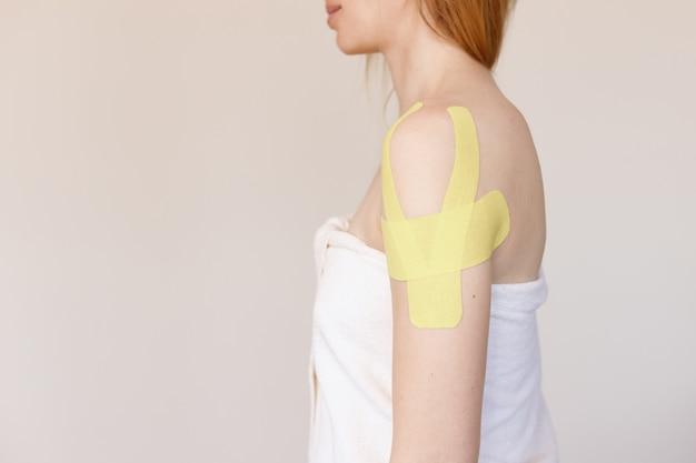 Vrouw met met lichaamsbanden op haar schouder