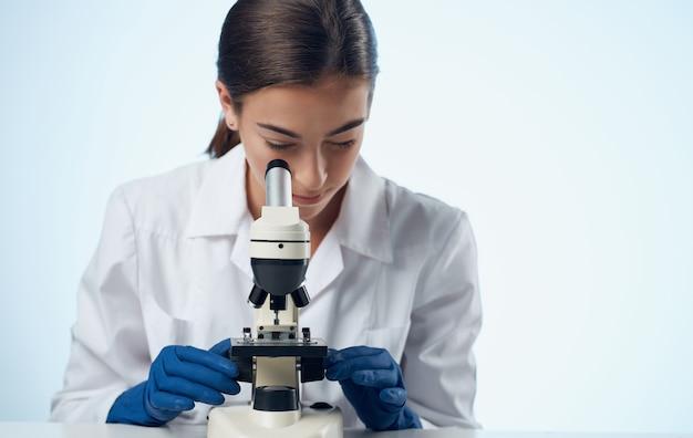 Vrouw met microscoop aan de tafel in laboratoriumonderzoek micro-organisme bacteriën.