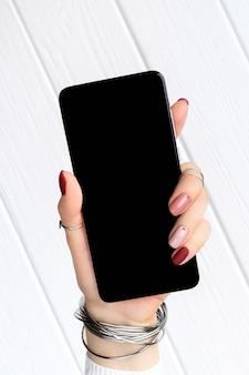 Vrouw met minimale roze lente zomer manicure ontwerp met smartphone. werk vanuit huis vrouwelijke bedrijfsconcept