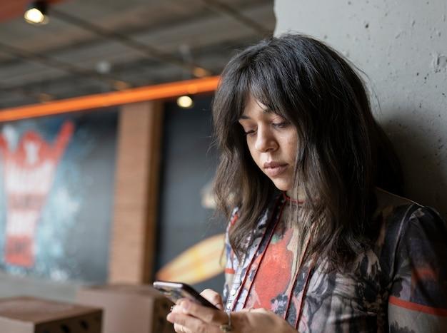 Vrouw met mobiel op een parkeerplaats
