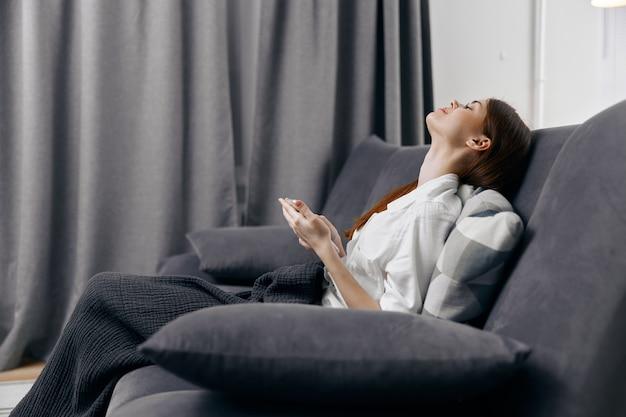 Vrouw met mobiele telefoon die op laag en gordijnen op de achtergrond omhoog kijken