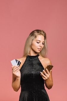 Vrouw met mobiele telefoon en creditcards