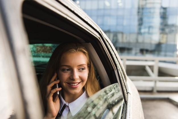 Vrouw met mobiele telefoon glimlacht in auto