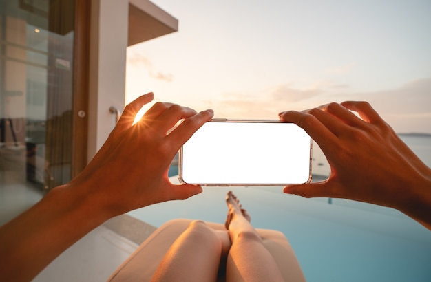 Vrouw met mobiele telefoon met leeg scherm terwijl ze op het zonnebed ligt met uitzicht op het strand.