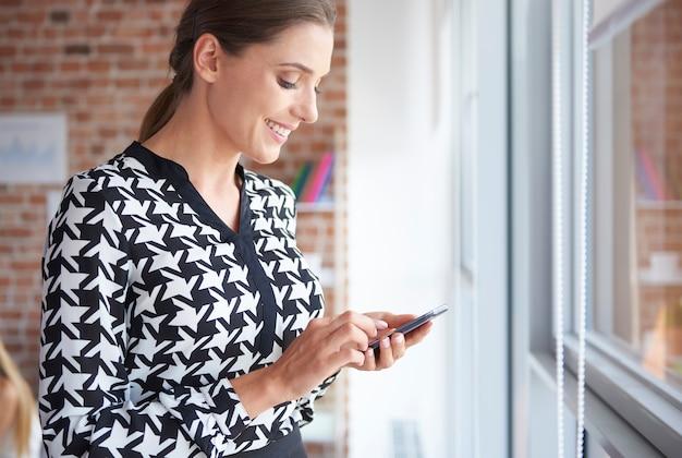 Vrouw met mobiele telefoon naast het raam