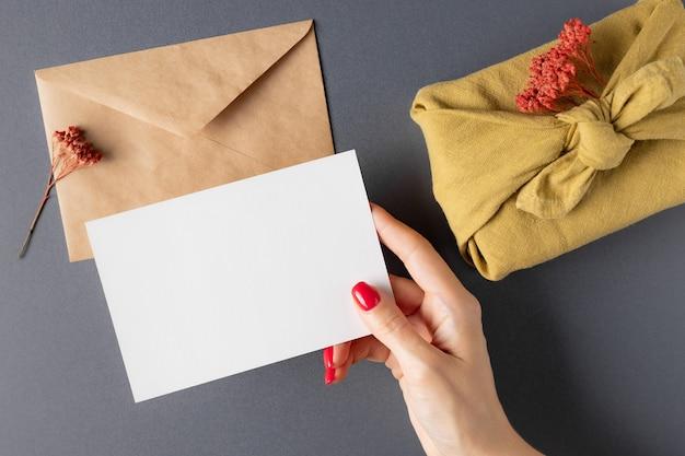 Vrouw met mockup kaart over grijze tafel met ambachtelijke envelop furoshiki cadeau