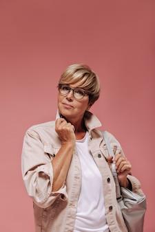 Vrouw met modern kort haar, oorbellen en coole bril in modieus jasje en licht t-shirt poseren met grijze tas op roze achtergrond.