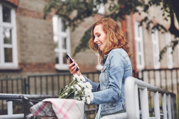 Vrouw met moderne mobiele telefoon in de stad
