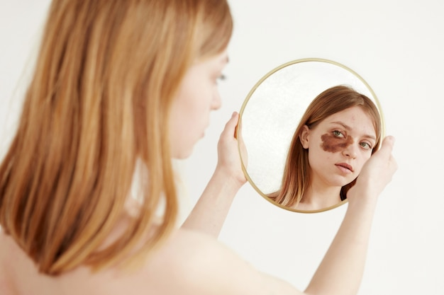 Vrouw met moedervlek op gezicht spiegel kijken