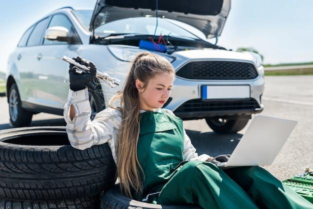 Vrouw met moersleutels en laptop onderhoud van gebroken auto