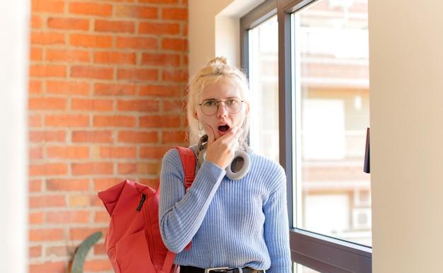 Vrouw met mond en ogen wijd open en hand op kin, die zich onaangenaam geschokt voelt, zegt wat of wauw