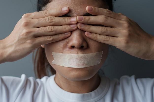 Vrouw met mond verzegeld in plakband. vrijheid van meningsuiting, persvrijheid, mensenrechten, protestdictatuur, democratie, vrijheid, gelijkheid en broederschapsconcepten