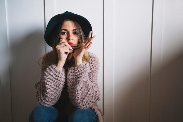 Vrouw met mondharmonica camera kijken