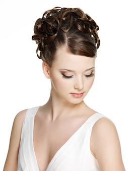 Vrouw met mooi kapsel en bruine make-up met lange valse wimper, op witte muur