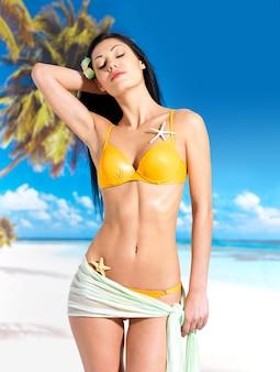 Vrouw met mooi lichaam in gele bikini bij strand