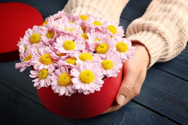 Vrouw met mooie bloemen in geschenkdoos op houten tafel