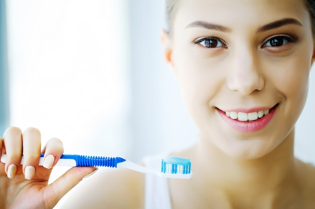 Vrouw met mooie glimlach, gezonde witte tanden met een tandenborstel. afbeelding met hoge resolutie