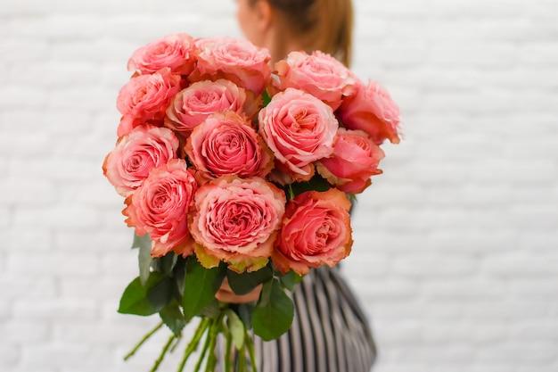 Vrouw met mooie pioenrozen. bloemboeket in vrouwelijke handen.