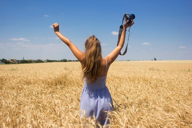 Vrouw met natuurlijk blond haar staande in een tarweveld met een camera