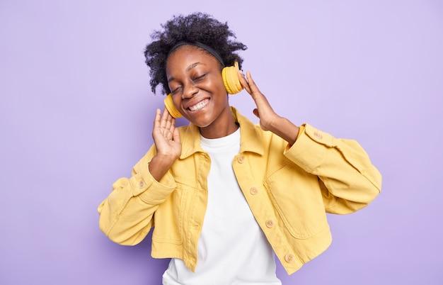 Vrouw met natuurlijk krullend haar houdt de koptelefoon ontspannen met muziek voelt plezier van goede audionummers draagt een gele jas geïsoleerd op een paarse muur