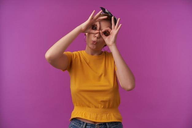 Vrouw met natuurlijke make-up draagt modieuze blouse en zwarte bandana met armen op gezicht show batman bril vingers emotie vreugde spelen dom poseren op paarse muur