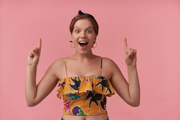 Vrouw met natuurlijke make-up en oorbellen dragen van stijlvolle trendy zomer doek glimlachend naar je wijzende vingers omhoog geïsoleerd poseren op roze