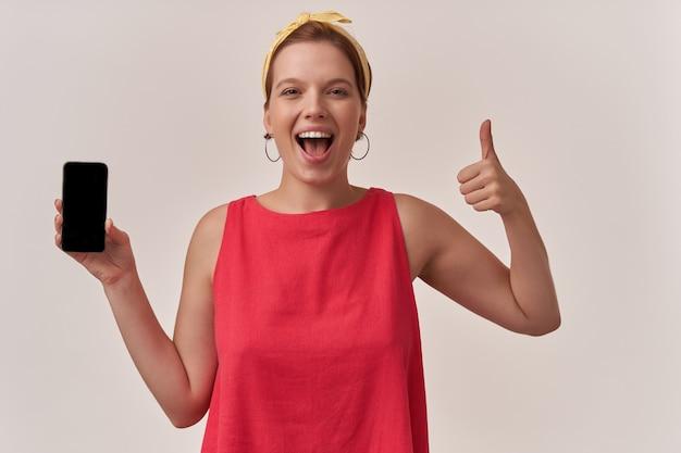 Vrouw met natuurlijke make-up en oorbellen lachend naar je muur met armen die telefoon vasthouden en grote vinger tonen emotie blij blij knipoog en lach naar je