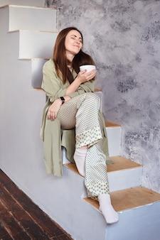 Vrouw met natuurlijke sproeten genieten van ochtendzon terwijl ze op de trap van haar huis zit.