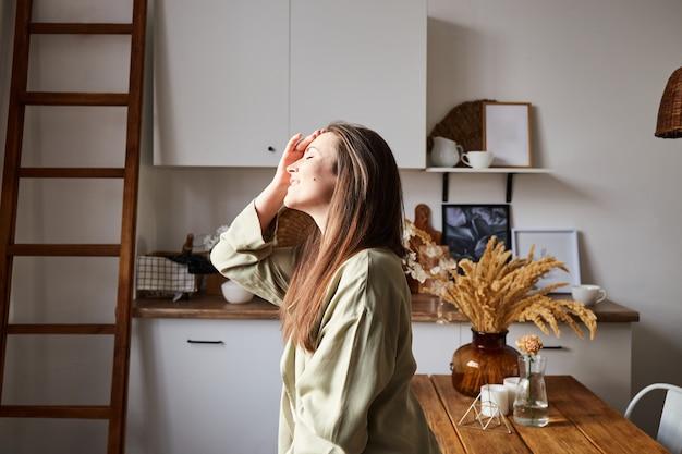 Vrouw met natuurlijke sproeten genieten van ochtendzonlicht op keuken in haar ecohuis.