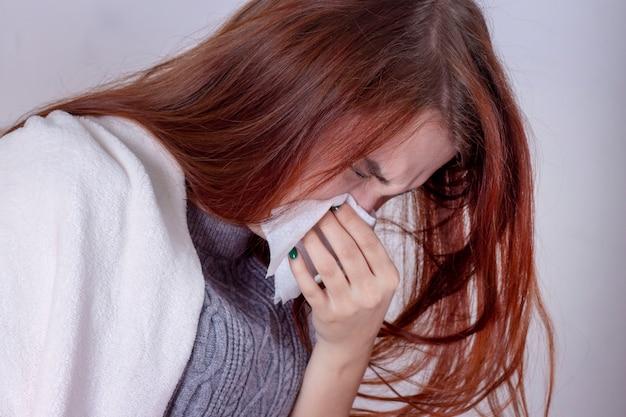 Vrouw met niezende neus die in weefsel blazen die aan de koude van de winter lijden en griepsymptomen die de pillen van geneesmiddeltabletten in ziekte en binnenlands gezondheidszorgconcept hebben