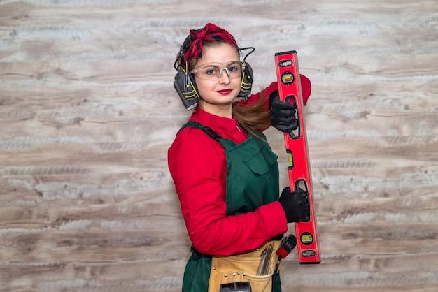 Vrouw met niveaumeting bij houten muur