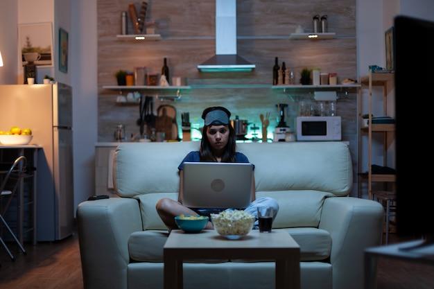 Vrouw met oogmasker die 's nachts laptop gebruikt terwijl ze tv kijkt en snacks eet. gelukkig persoon in pijamas zittend op de bank lezend schrijvend zoekend browsen op notebook met internet die mails controleert checking