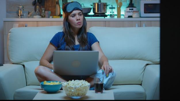 Vrouw met oogmasker die 's nachts laptop gebruikt terwijl ze tv kijkt en snacks eet. gelukkig persoon in pijamas zittend op de bank lezend schrijvend zoekend browsen op notebook met internet die mails controleert