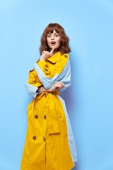 Vrouw met open mond in een gele jas houdt een vinger in de buurt van haar gezicht op een blauwe achtergrond copy space